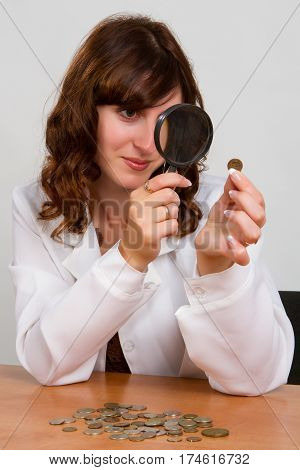 Financial concept hand hold magnifying glass and coins
