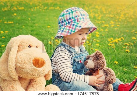 sad boy sitting with softtoys outoors. Thoughtful child with teddy and plush dog on the field with dandelions in spring