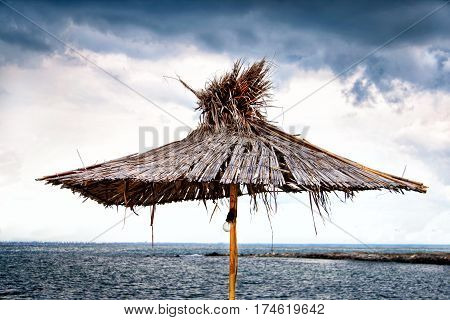 Beach umbrella of the reed on the background of cloudy sky and sea