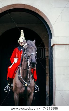 LONDON, UK - DECEMBER 24, 2016: The Queen's Life Guard of the Queens Household Cavalry on duty on his horse in an archway at Horse Guards Parade facing Whitehall.