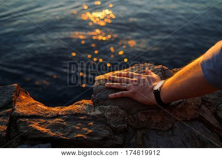 Close up shot of men's left hand on a rock, wearing a simple wedding band and a watch. Sea and sunset light trails on the background.