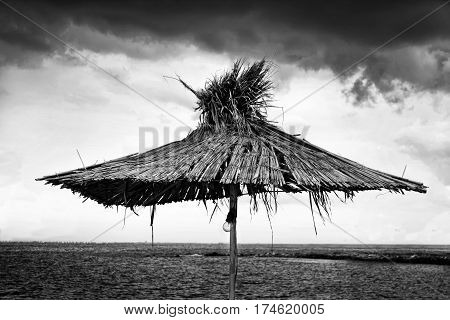 Black and white beach umbrella of the reed on the background of cloudy sky and sea