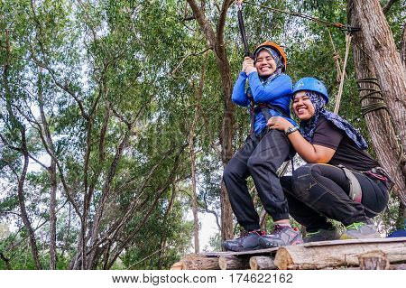 Labuan,Malaysia-Feb 12,2017:Happy muslim girls ready to play on a flying fox in Labuan,Malaysia.There will be more ziplines in Malaysia,especially when there have so much natural resources & rainforest.