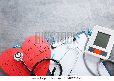 White Electric Tonometer With Stethoscope On Grey Wooden Table