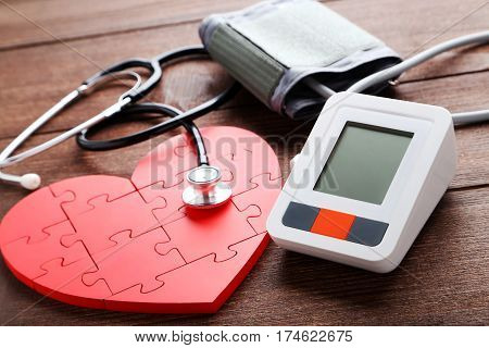 White Electric Tonometer With Stethoscope On Brown Wooden Table