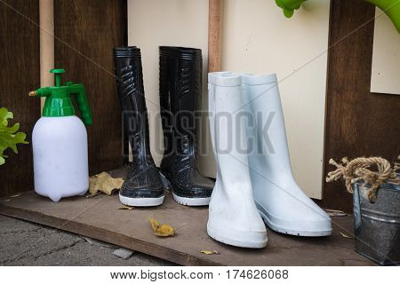 Gardening tools white boots and black boots.