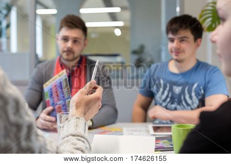 Business Discussion at grey Table in Office Meeting Room young People Men and Woman Man pointing with white Pen convincing Opponents focus on Hand