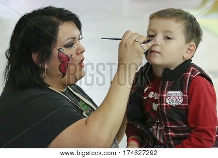 TUCSON, ARIZONA, FEBRUARY 20. The Tucson Expo Center on February 20, 2017, in Tucson, Arizona. A Face Painter at T-Rex Planet at the Tucson Expo Center in Tucson, Arizona.