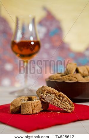 Closeup of Italian cantucci biscuits over a red napkin and a glass of vin santo wine on background