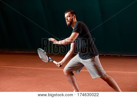 Handsome young man in t-shirt holding tennis racket and looking concentrated while standing on tennis court