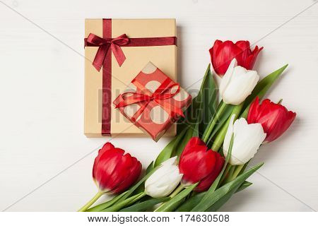 Red and white tulips on a light background with a gifts. Concept of spring Women's Day Mother's Day 8 March the holiday greetings. Place for your text