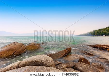 calmness sea in the morning sunrise with bright blue sky and rocks rayong province thailand
