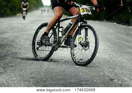 V.Ufaley Russia - August 09 2015: man racer cyclist mountainbiker downhill on gravel road during bicycle race