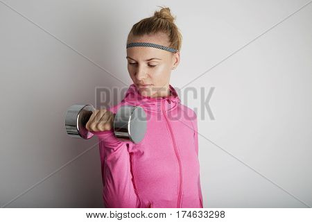 Portrait of fitness young woman wearing pink sports wear. Fresh healthy stylish sport girl posing close to white wall.