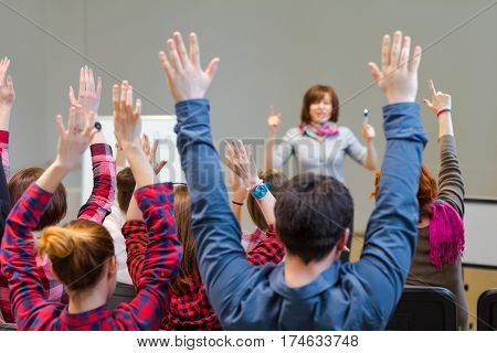 Diverse Group of Students in Conference Room raising Arms up actively participating in Seminar Teachers Body on background