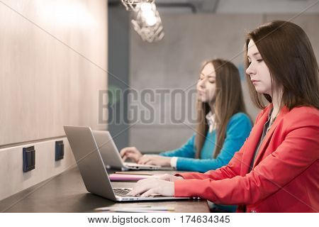 Two young Women in red and blue Jacket working on Laptop Computers at wooden Bar Counter one smiling another with serious undistracted Face Expression