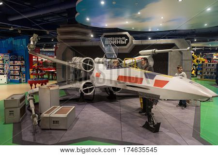 Moscow Russia - March 5 2017: Child sitting in decorative star wars x-wing starfighter in the toy store.