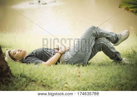 Young Woman Listening To Music From Your Smart Phone On The Grass