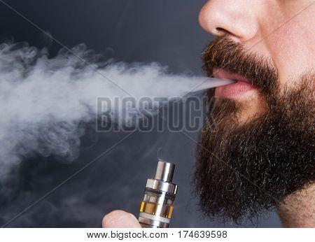 a beared man smoking a  electronic cigarette