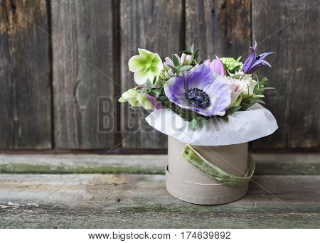 Bouquets of pink and violet flowers in the box on a woden background close up