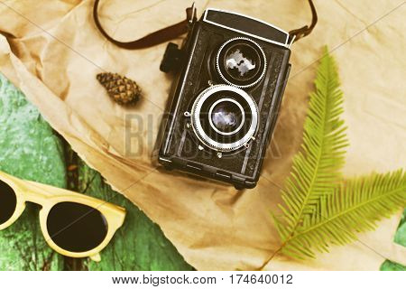 Old retro camera with sunglasses on vintage wooden boards abstract background
