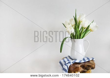 Still life with tulips bouquet in white vase on wooden rustic chair