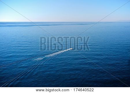 Speed boat in clear blue water of Mediterranean Sea, heading off the coast of Cinque Terre, Italy, on a sunny day with clear blue sky.
