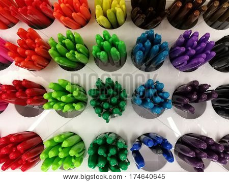 Colorful pen on shelves in stationery store or department store focus-on-foreground bule ball pen with blur background Colorful highlight pen on shelf color pen on circle hole