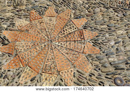 Patterned floor with sea pebbles red bricks and metal gears in the park Montjuic Barcelona Catalonia Spain