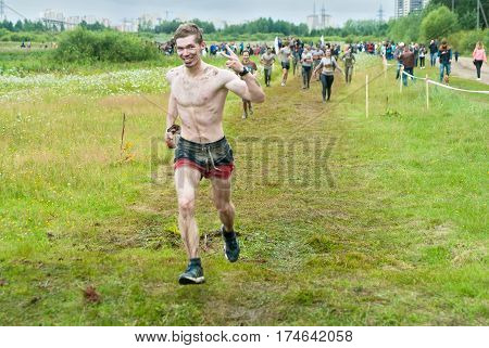 Tyumen Russia - August 8 2015: Steel Character extrim race on Krugloe lake. Gagarin park in Cape district. Running after obstacle stage - to get on inclined wall and to jump off in ditch with water