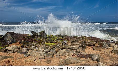Waves pounding a rock strewn beach under a blue sky