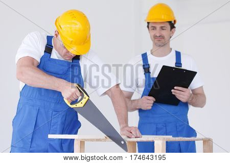 Two workmen in protective workwear with saw and folder