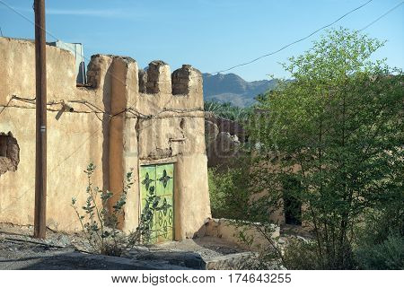 A derelict old earthen house in ruin under a clear sky