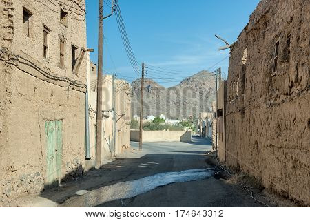 An empty street between derelict old earthen houses in ruin