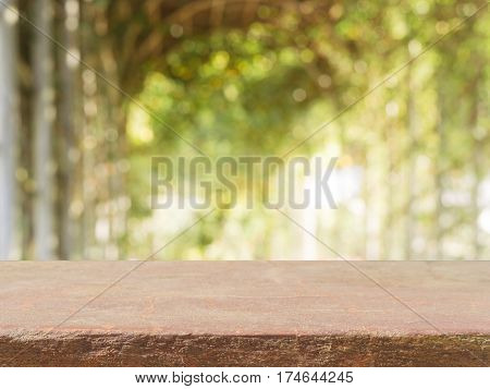Stone board empty table top in front of blurred background. Perspective brown stone table top over blur trees in forest - can be used for display or montage your mock up products. spring season.