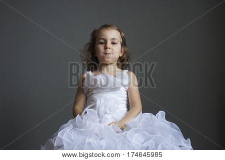 Little girl in a smart white dress. Human emotions. Joke tomfoolery