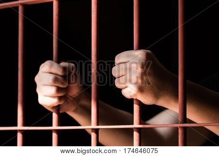 Close up hand of woman prisoner holding old iron bar in jail.