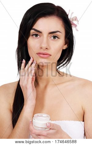 Beautiful woman rubs cream face, isolated on white background