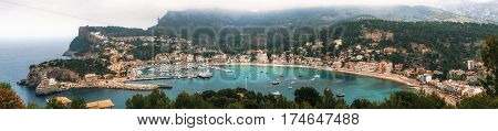 Panoramic view of Port de Soller with harbour yachts tourist boats colorful architecture and beach on a cloudy day. Landmark of Mallorca Spain
