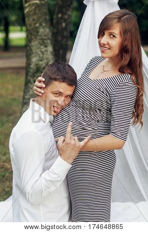 Happy Romantic Family Portrait, Funny Husband Kneeling And Smiling Near Beautiful Pregnant Wife, Exp