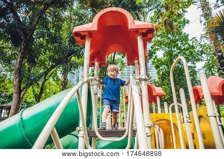 Happy Little Kid Boy Playing At Colorful Playground. Adorable Child Having Fun Outdoors