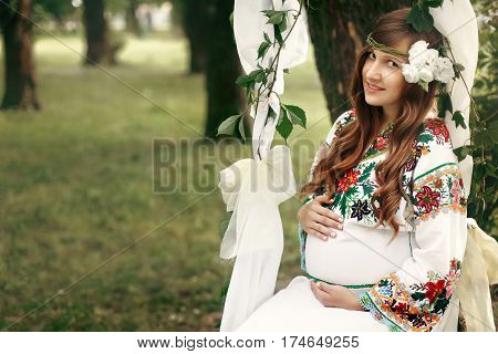 Beautiful Pregnant Brunette Woman In Embroidered White Dress On Fairytale Swing In Park. Tender Mome