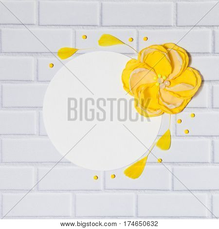 White Square Background With Handmade Gentle Yellow Flower and Feathers, Lying Flat on the White Brick Wall, Top View. Have an Empty Circle Place For Your Text.