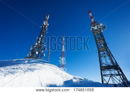 Tree telecommunication towers on snowcapped mountain against blue sky