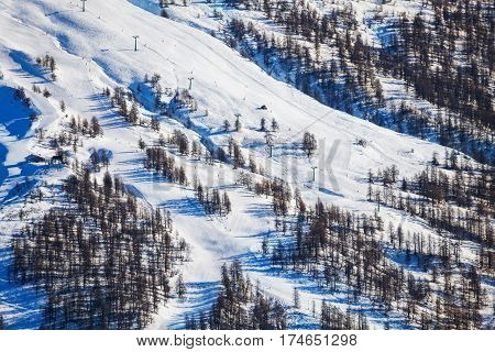 Top view picture of snowy mountains with steep slopes at alpine ski resort in the winter