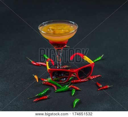 colored drink a combination of red orange lemon martini glass brown sunglasses red and green peppers party set