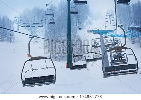 Aerial ropeway with empty chairlifts at ski resort at foggy winter day