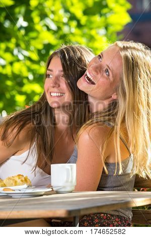 Close-up side portrait of two beautiful happy young women sitting close in street cafe and laughing against green foliage in sunny day