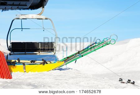 Empty rescue sleds standing next to chairlift at ski resort