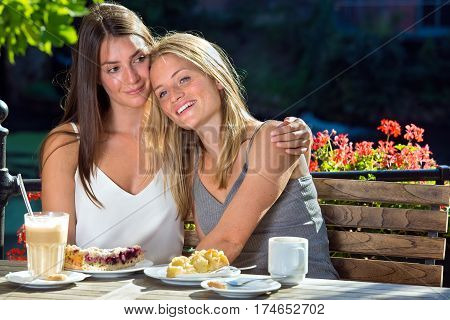 Two Girls Hugging In Outdoor Cafe